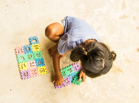 Girl playing jigsaw on the cement ground  photo