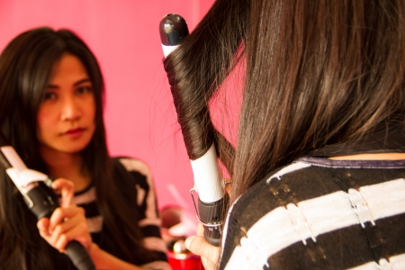 curling irons: Asian girl dressing her hair with electric hair roll