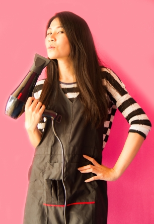 Hair stylist holding electric hair dryer on the pink background  photo
