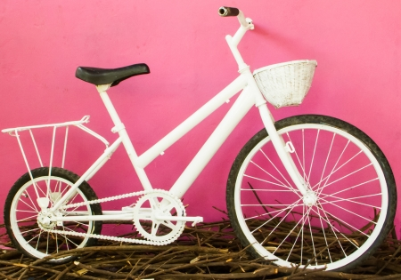 Vintage white bicycle on the pink wall. photo