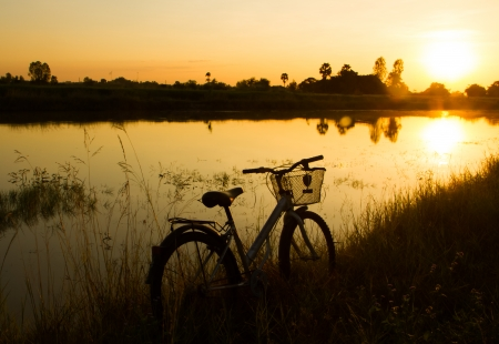 Silhouette of bicycle beside the pond in the evening. photo