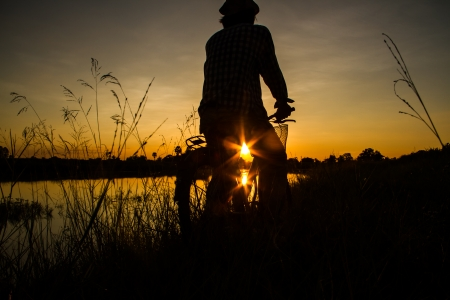 Farmer riding bicycle beside the pond with sunset view. photo