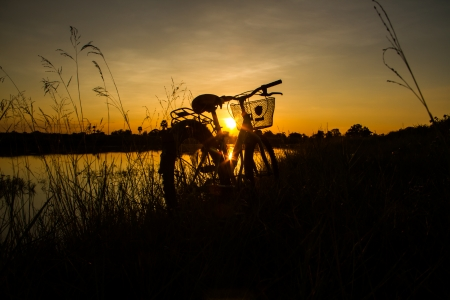 Silhouette of bicycle beside the pond in the evening  photo