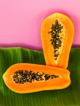 half cut: Papaya half cut with seeds inside on banana leaf