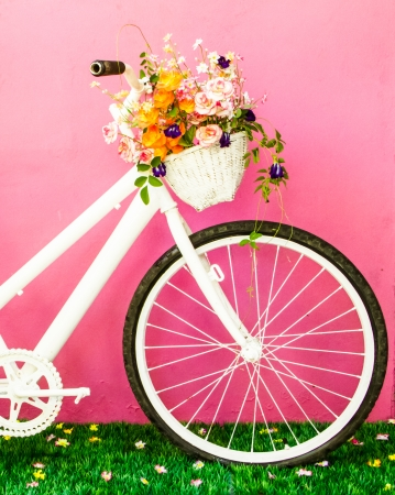 White vintage bicycle with flowers on the pink wall