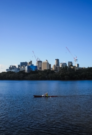 Canoeing in the river with Brisbane city background. photo