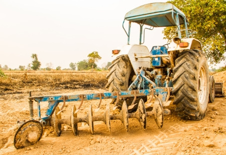farm implement: Plowing tracktor in the rice farm background