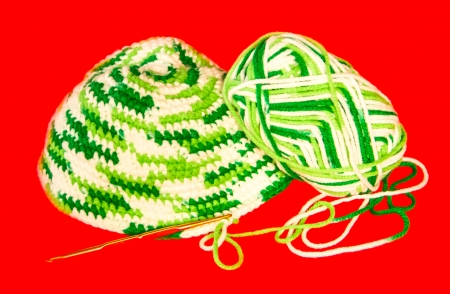 purl: Green and white knitwear material on red background.