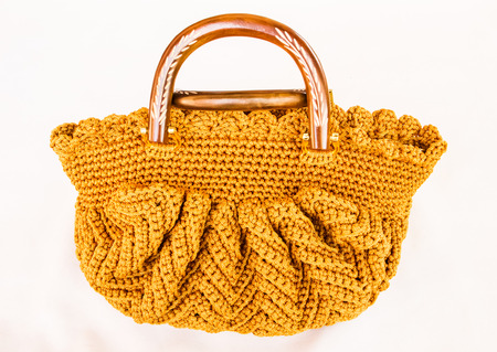 Gold crocheting hand bag on the white . photo