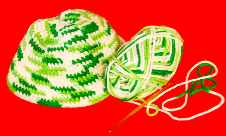 Green and white knitwear material on red . Stock Photo