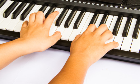 Children hands playing musical keyboard. photo
