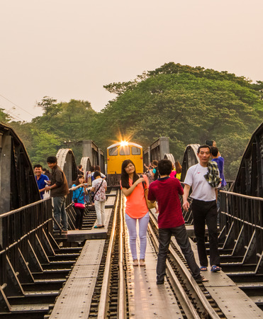 KANCHANABURI,THAILAND-MARCH 13 : People taking photo with the running train on the bridge on the river Kwai on March 13,2014.This bridge remind of second world war.