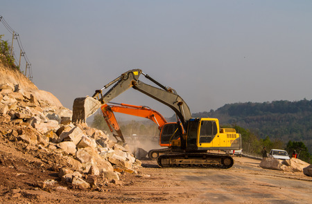 Loader excavators moving the rock from the road. photo