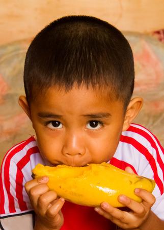 Asian boy eating yellow mango.