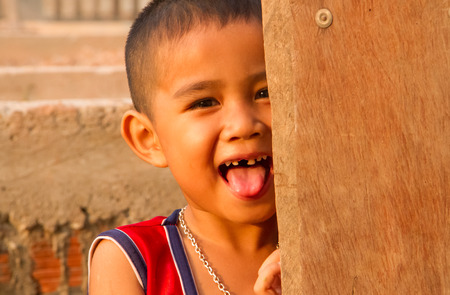 Asian boy smiling behind the door. photo