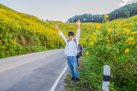 one lane road sign: Asian man hitchhiking  on the flower field road.