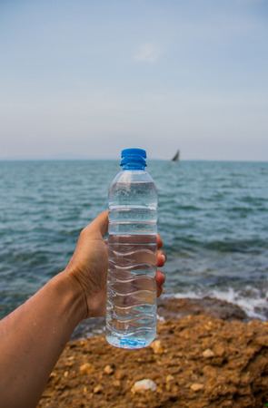clear waters: Drinking water bottle holding by hand   beside the sea.
