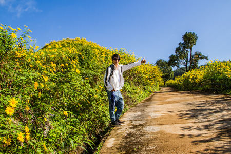 one lane sign: Asian man hitchhiking  on the flower field road.