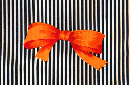 abstract paint: Orange bow on black and white strips.