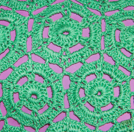 Green knitting texture on pink background. photo