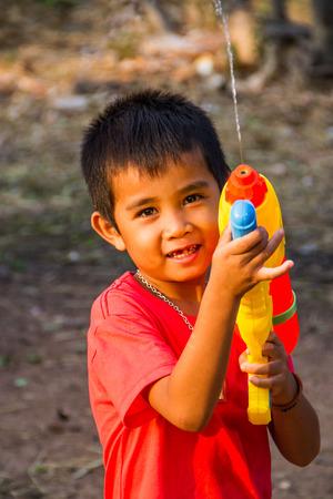 water gun: Boy shooting water gun in the summer time. Stock Photo