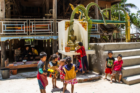 SAVANNAKHET,LAOS-APRIL 16 : Buddhist children come to shower buddha image in the temple to celebrate  Songkran festival in Savannakhet,Laos on April 16,2015.Songkran festival is Laos new year. photo