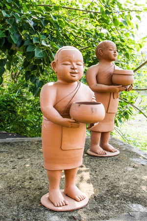 alms: Buddhist novice holding alms bowl clay dolls.