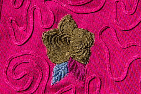 lappet: Flower sewing on pink fabric. Stock Photo