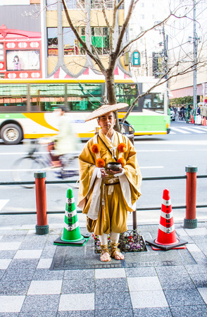 develope: TOKYO,JAPAN-APRIL 2 : Japanese priest holding alms-bowll to get donation in Tokyo,Japan on  April 2,2015.Donation money will spend to develope the temple. Editorial