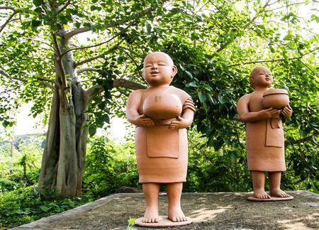 limosna: Novatos sosteniendo ofrendas budistas rodar muñecos de barro.
