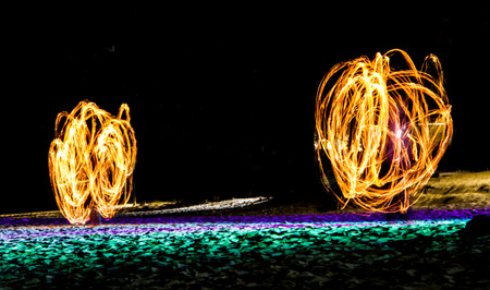Swing fire show on the beach. Stock Photo