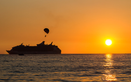Beautiful sunset at the ocean with silhouette of ship. photo