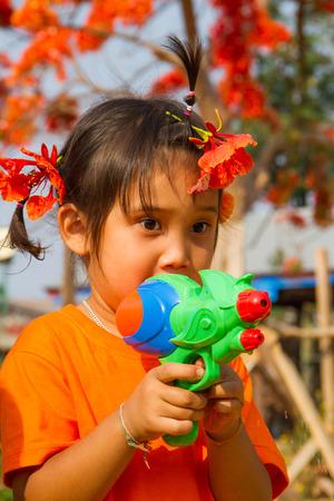 water gun: Girl shooting water gun in summer time.