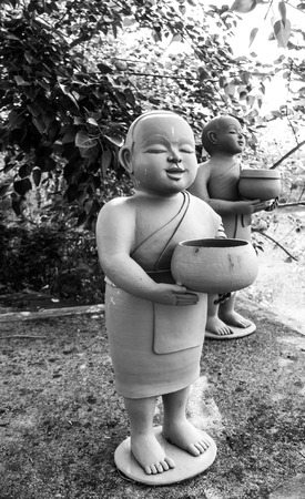 novice: Buddhist novice holding alms bowl clay dolls.