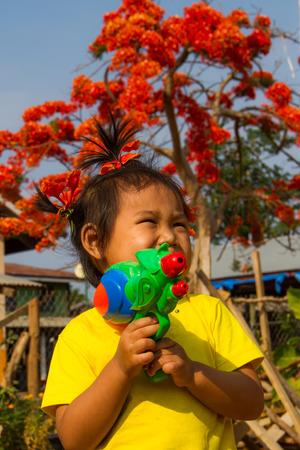 water gun: Girl holding water gun in summer time. Stock Photo