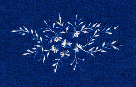 lappet: Abstract flower sewing on blue fabric. Stock Photo