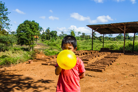 earthen: Asian boy blowing up the balloon on dry earthen brick background.