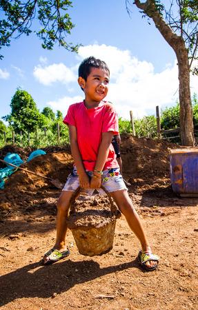 earthen: Asian boy holding heavy earthen brick ingredients. Stock Photo