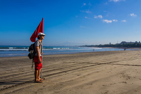 Model hold red flag at Kuta beach.