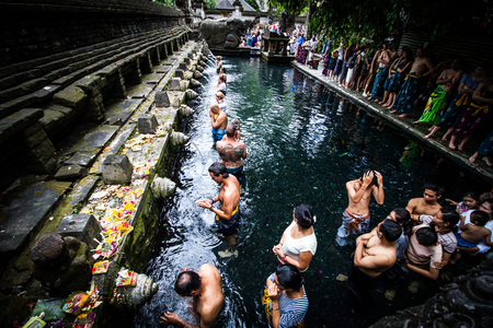 religion ritual: BALI,INDONESIA - AUGUST 19, 2016: Balinese Hindu and tourist  wash themselves in a ritual at the pool in Pura Tirta Empul ,  Bali. Hinduism is the religion of the original Balinese inhabitants. Editorial