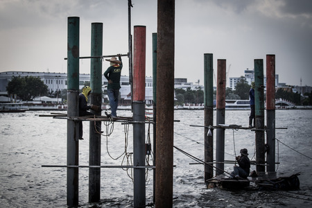 bridge footing: BANGKOK, THAILAND - AUGUST 17 : Unidentified workers work on construction site over the river on August 17, 2016 in Bangkok, Thailand.
