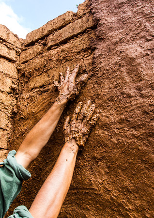 Builder hand while plastering wall in earthen house. Stock Photo