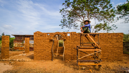 Builder sitting with earthen house background.