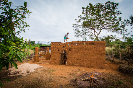 Builder building earthen house on top of the wall.
