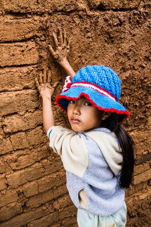 The girl plastering earthen house.