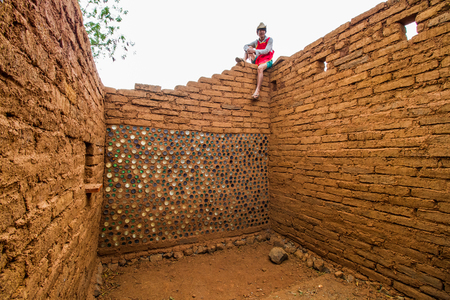 adobe wall: Builder sitting on top of the wall of earthen house.
