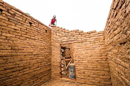Builder building earthen house by earthen brick. Stock Photo