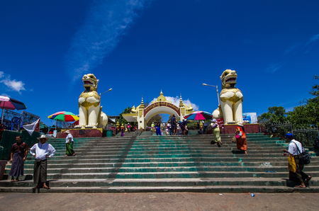 KYAIKTIYO,MYANMAR-MARCH 13,2017: People are going to the entrance of the Kyaiktiyo Pagoda site, Golden Rock, with two lion guardians. Kyaiktiyo Pagoda also known as Golden Rock is a well known Buddhist pilgrimage site in the Mon State, Myanmar. Редакционное