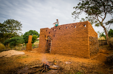 Builder sitting on top of the wall of earthen house.