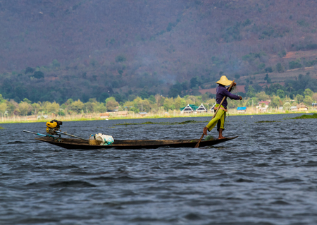 INLE LAKE,MYANMAR-MARCH  11,2017. Fisherman control the boat by feet on  Inle Lake in Shan, Myanmar. Inle Lake is a freshwater lake located in the Nyaungshwe Township of Shan State. Editorial